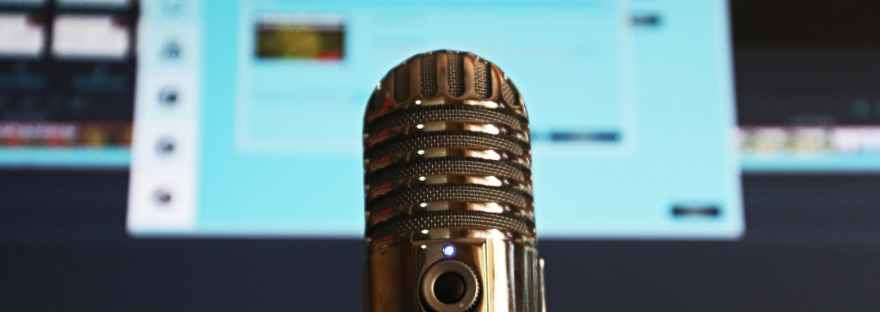 Shiny silver microphone in front of a blurry monitor.