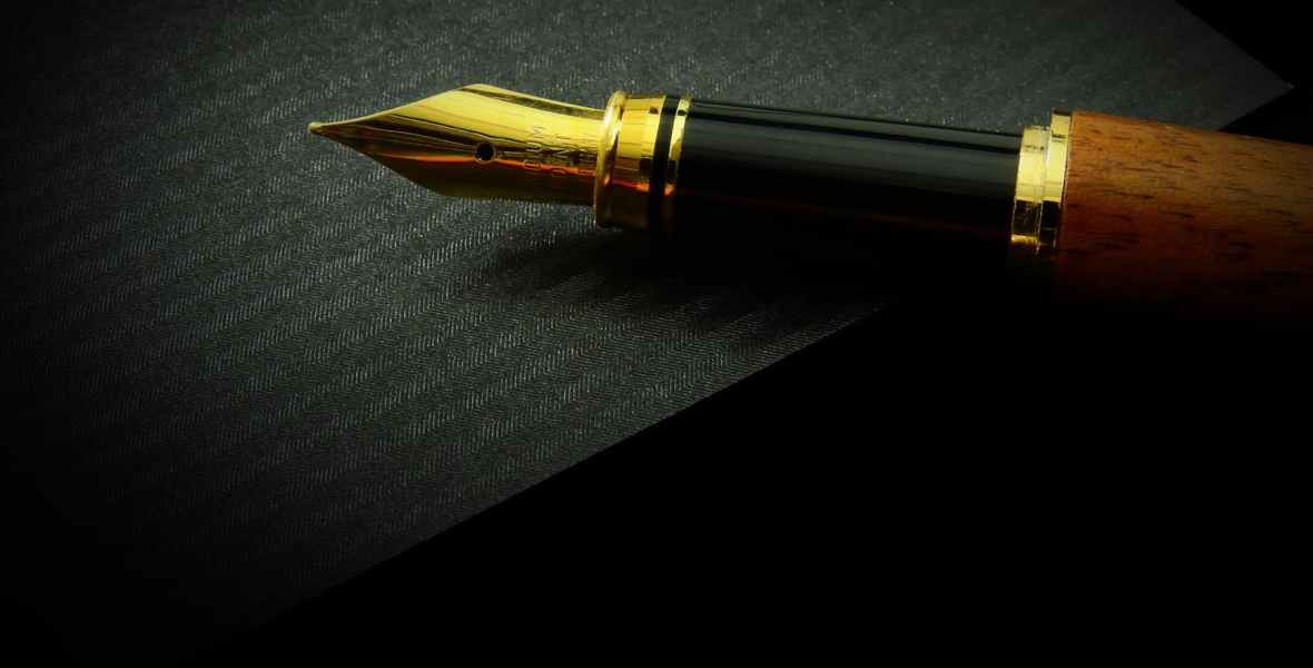 Opened fountain pen, focus on the nib, on a black surface.