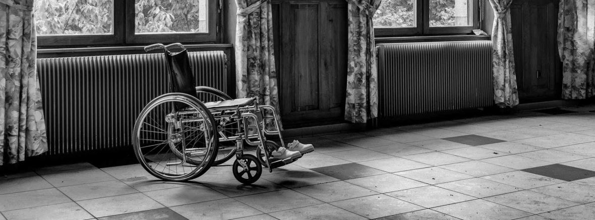 Black and white photo of an empty wheelchair in a bright but empty room.